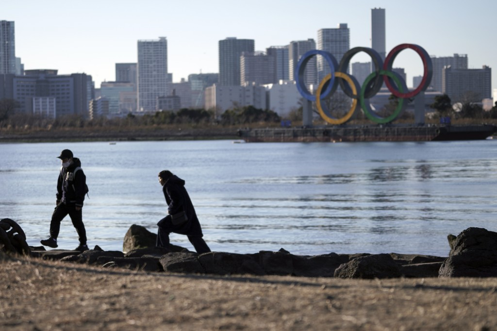 A man and a woman walk near the Olympic rings floating in the water in the Odaiba section in Tokyo Wednesday, Jan. 20, 2021. The postponed Tokyo Olymp...