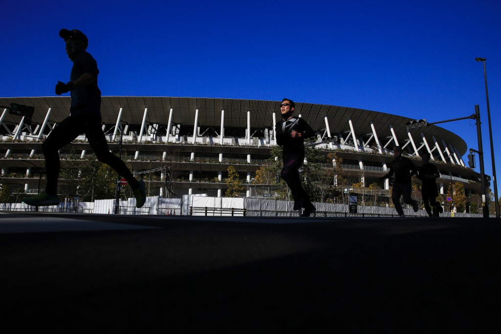 Runners pass by Japan National Stadium, where opening ceremony and many other events are planned for postponed Tokyo 2020 Olympics, Thursday, Jan. 21,...