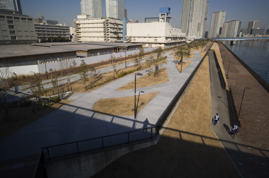 Security guards, bottom right, pass by each other as they patrol the closed area of the riverbank adjacent to a closed building complex, back left, bu...