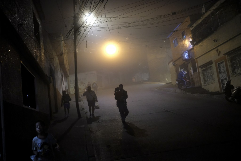 FILE - In this Jan. 6, 2021 file photo, residents walk in the Catia neighborhood of Caracas, Venezuela, amid the new coronavirus pandemic. Although th...