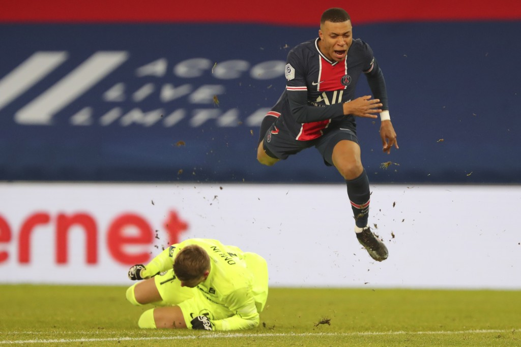 PSG's Kylian Mbappe, right, jumps over Montpellier's goalkeeper Jonas Omlin during the French League One soccer match between Paris Saint-Germain and ...