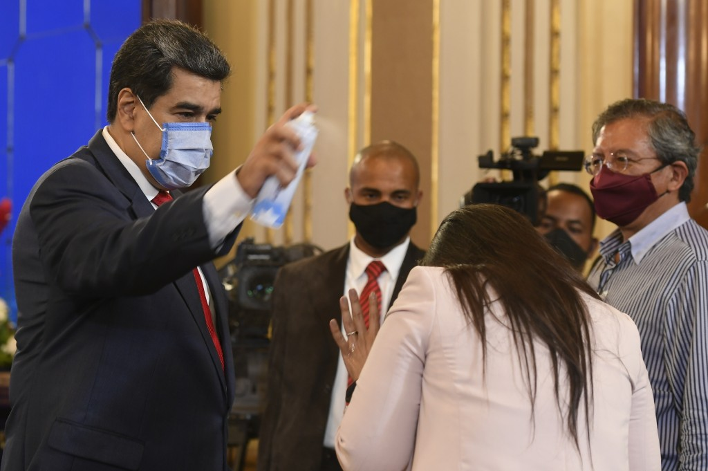 FILE - In this Dec. 8, 2020 file photo, Venezuela's President Nicolas Maduro playfully sprays a journalist with disinfectant as he exits a press confe...