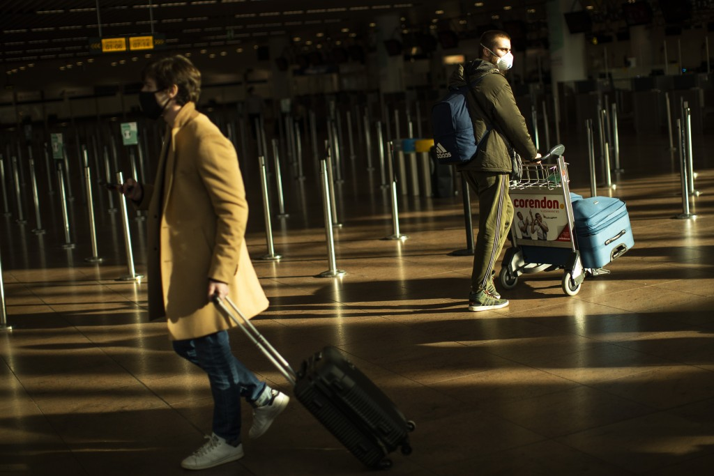 Travellers, wearing face masks to prevent the spread of the coronavirus COVID-19, walk along the departure hall of the Zaventem international airport ...