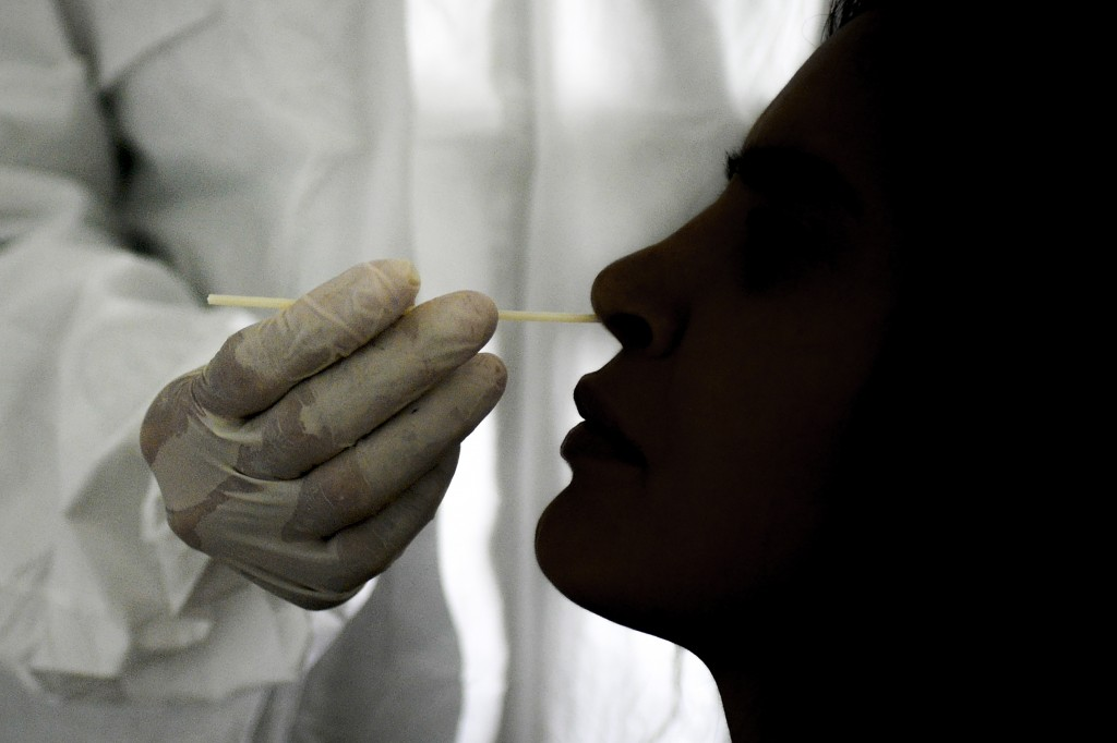 FILE - In this Sept. 19, 2020 file photo, a doctor takes a nasal swab sample to test for COVID-19 at the Cocodrilos Sports Park in Caracas, Venezuela....