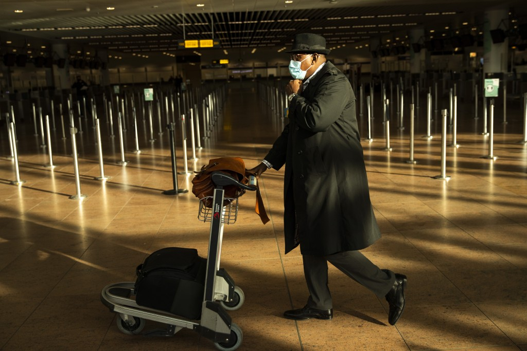 A traveller, wearing a face mask to prevent the spread of the coronavirus COVID-19, walks along the departure hall of the Zaventem international airpo...