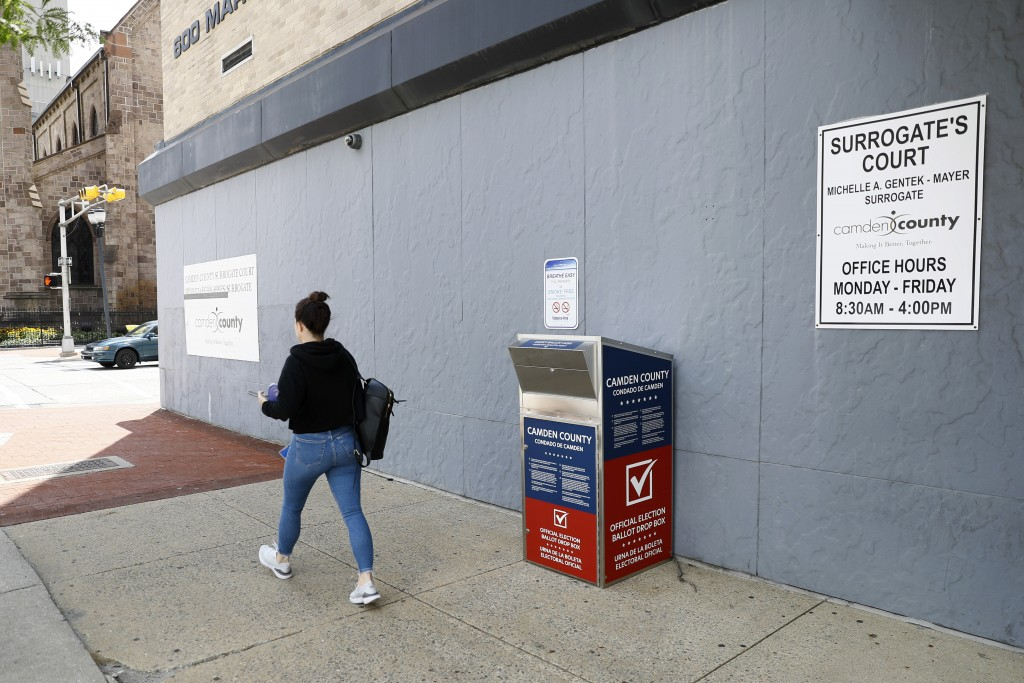 FILE - In this July 1, 2020, file photo, a woman walks past a vote-by-mail drop box for the upcoming New Jersey primary election outside the Camden, N...