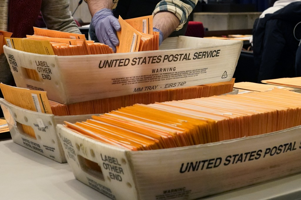 FILE - In this Nov. 2, 2020, file photo, Election officials sort absentee and early voting ballots for counting inside Boston City Hall in Boston. Dem...