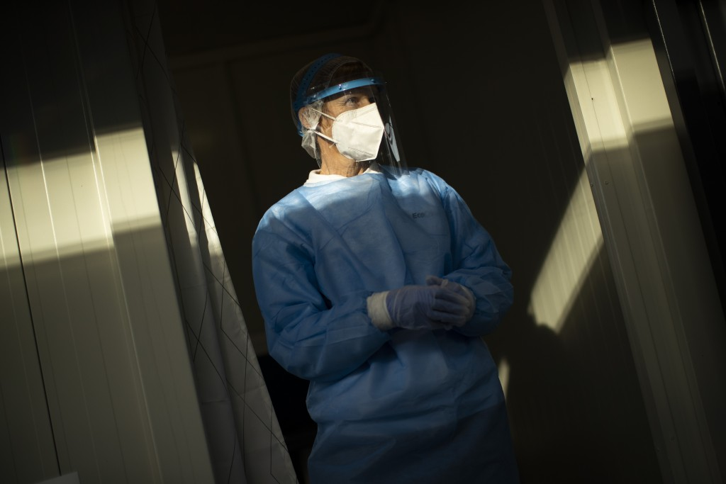 A medical worker, wearing a full protective gear, waits for travellers to be tested for COVID-19 at the Zaventem international airport in Brussels, Fr...