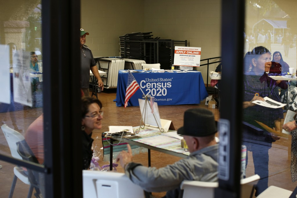 FILE - In this Feb. 8, 2020, file photo, people volunteer to get people registered to vote and a booth offering employment for the upcoming 2020 censu...