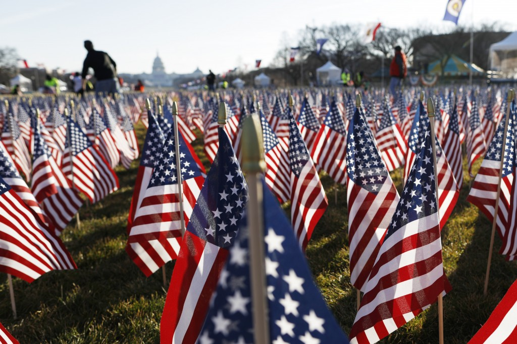 FILE - In this Jan. 21, 2021, file photo workers begin to remove a display of flags on the National Mall one day after the inauguration of President J...