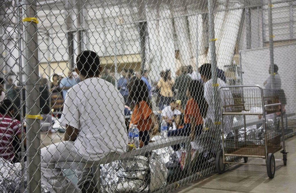 FILE - In this June 17, 2018, file photo provided by U.S. Customs and Border Protection, people who've been taken into custody related to illegal entr...