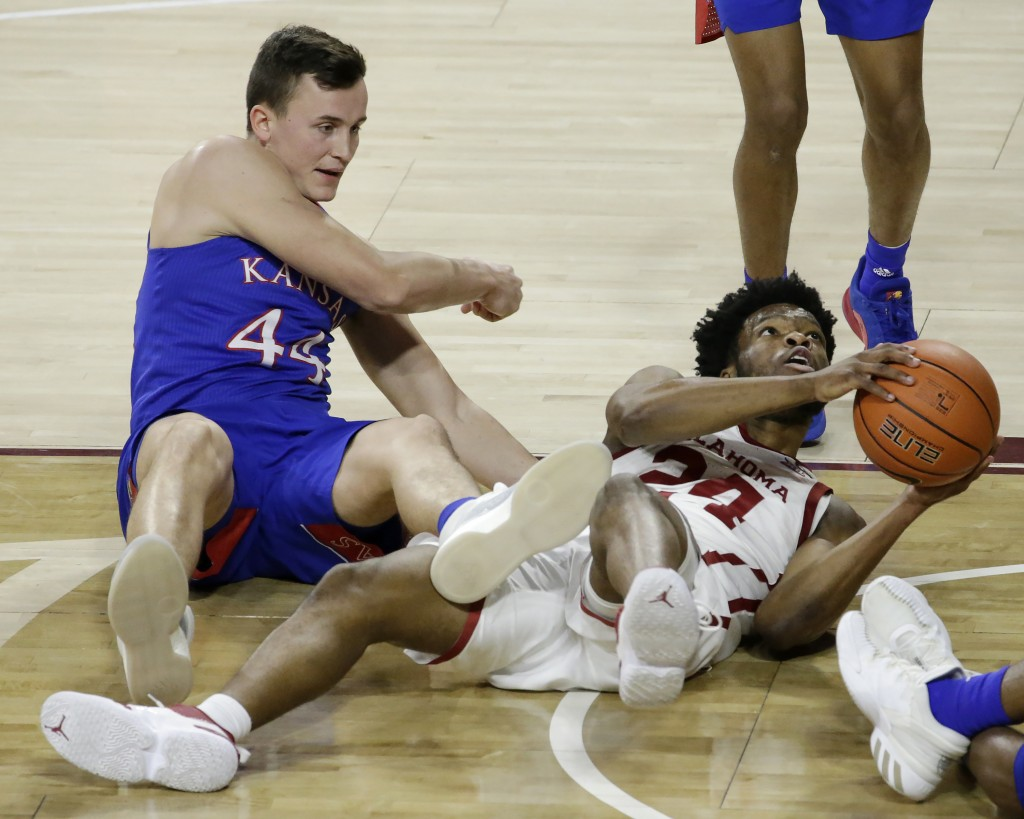 Oklahoma guard Elijah Harkless (24) and Kansas forward Mitch Lightfoot (44) fight for the ball during the second half of an NCAA college basketball ga...