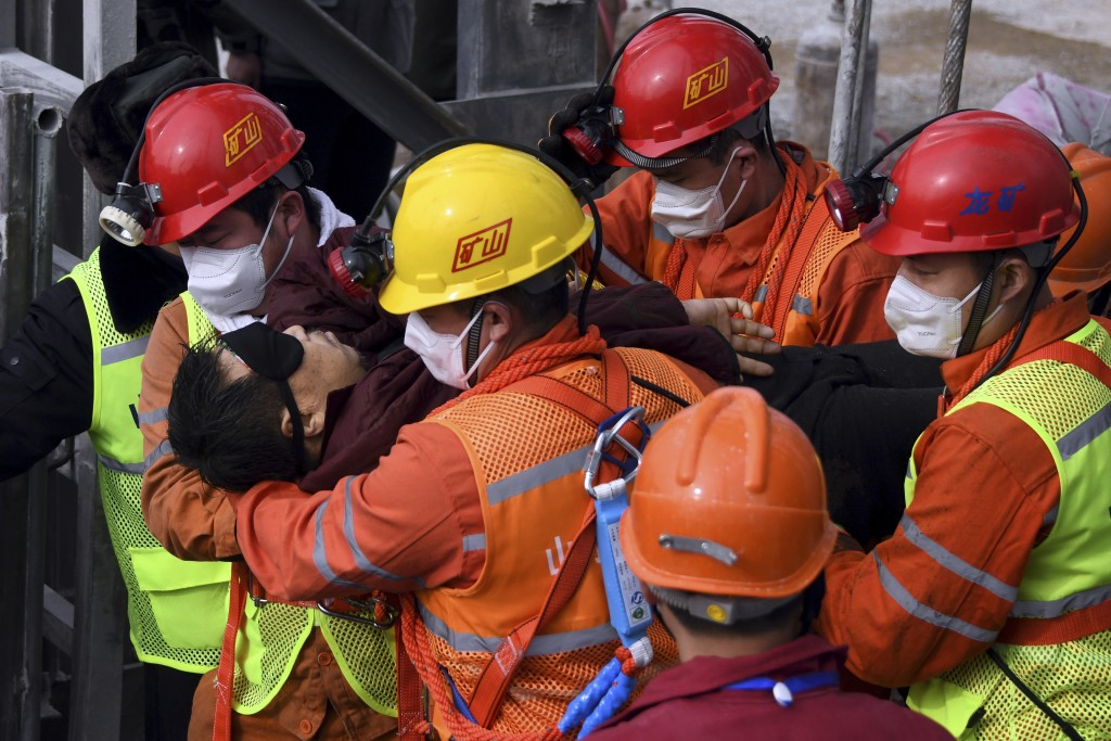 In this photo released by Xinhua News Agency, rescuers carry a miner who was trapped in a mine to an ambulance in Qixia City in east China's Shandong ...