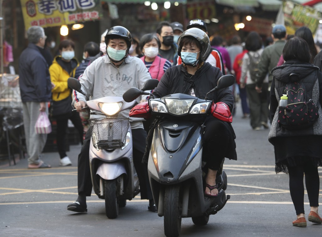 People wear face masks to help curb the spread of the coronavirus as they ride scooters near  a market in Taipei, Taiwan, Monday, Jan. 25, 2021. (AP P...