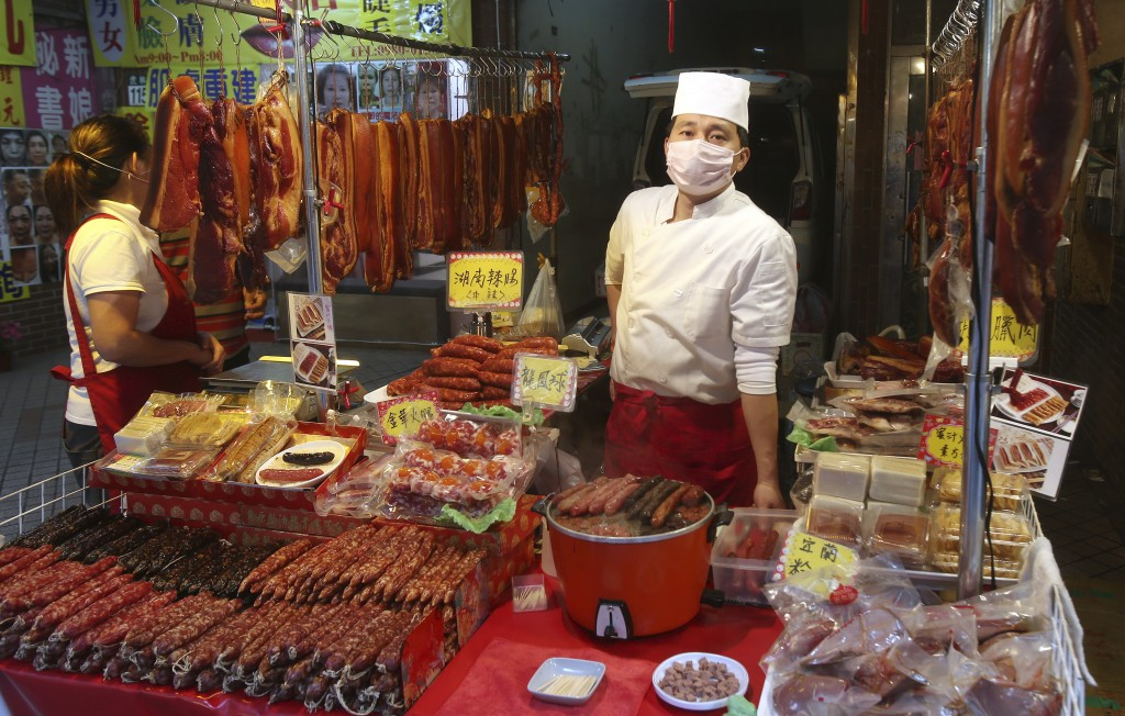 A vendor wears a face masks to help curb the spread of the coronavirus at his shop at a market in Taipei, Taiwan, Monday, Jan. 25, 2021. (AP Photo/Chi...