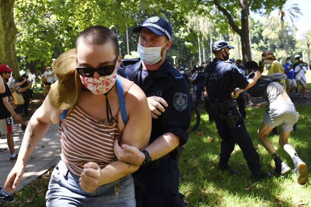 Protesters scuffle with police as they are arrested when a small group marched through Hyde Park following an Invasion Day rally in Sydney, Tuesday, J...