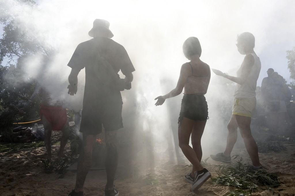 Members of the public participate in an Aboriginal smoking ceremony during Australia Day ceremonies in Sydney, Tuesday, Jan. 26, 2021. (AP Photo/Rick ...