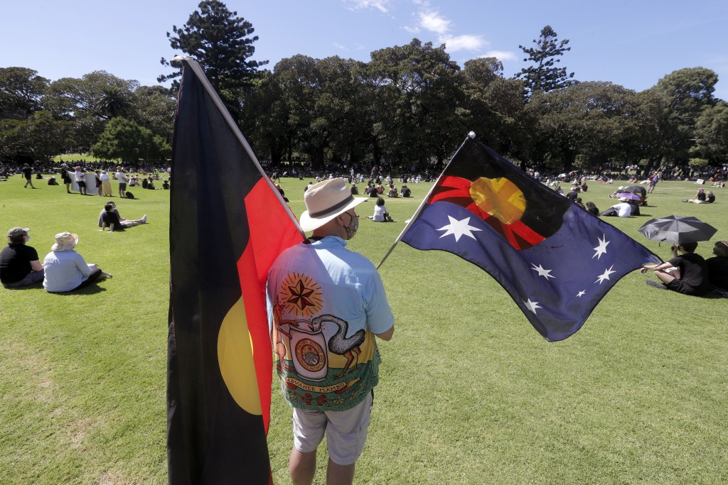 A man holds a modified Australian flag and the Aboriginal flag in a social distanced crowd during an Aboriginal-lead Invasion Day rally on Australia D...
