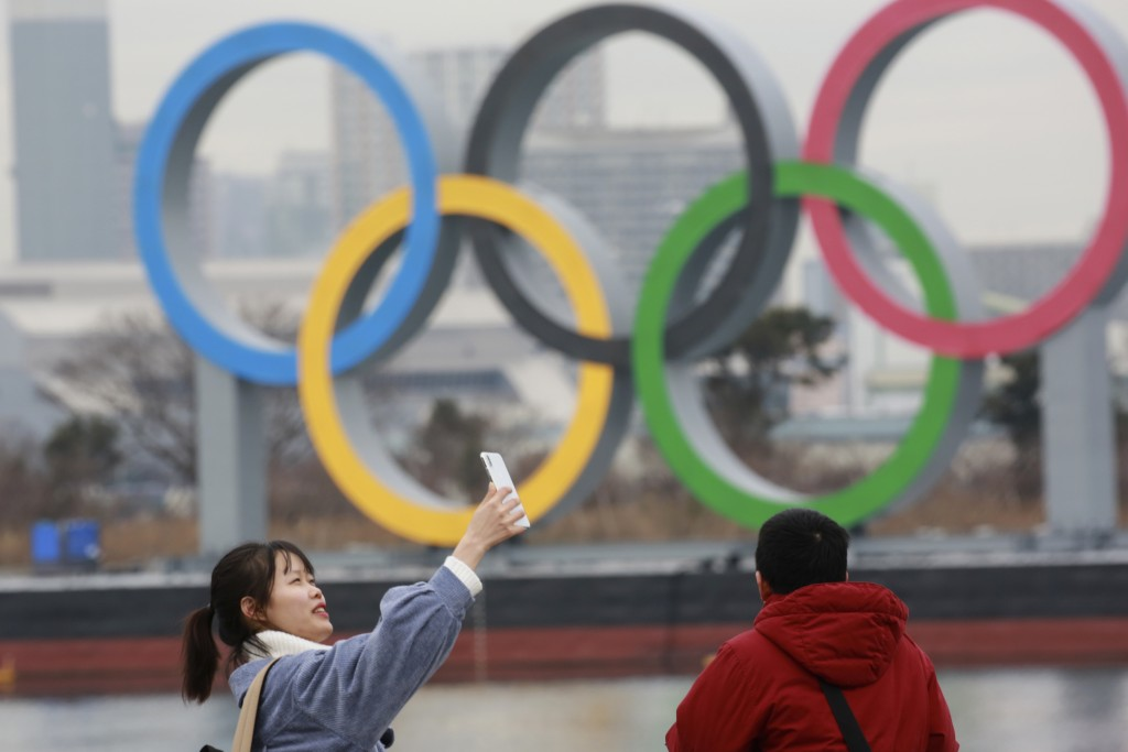A woman poses for a selfie in front of Olympic rings at Odaiba waterfront in Tokyo, Tuesday, Jan. 26, 2021. The postponed Tokyo Games are scheduled to...