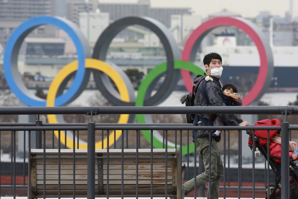 People wearing face masks to protect against the spread of the coronavirus walk on the Odaiba waterfront as Olympic rings is seen in the background in...