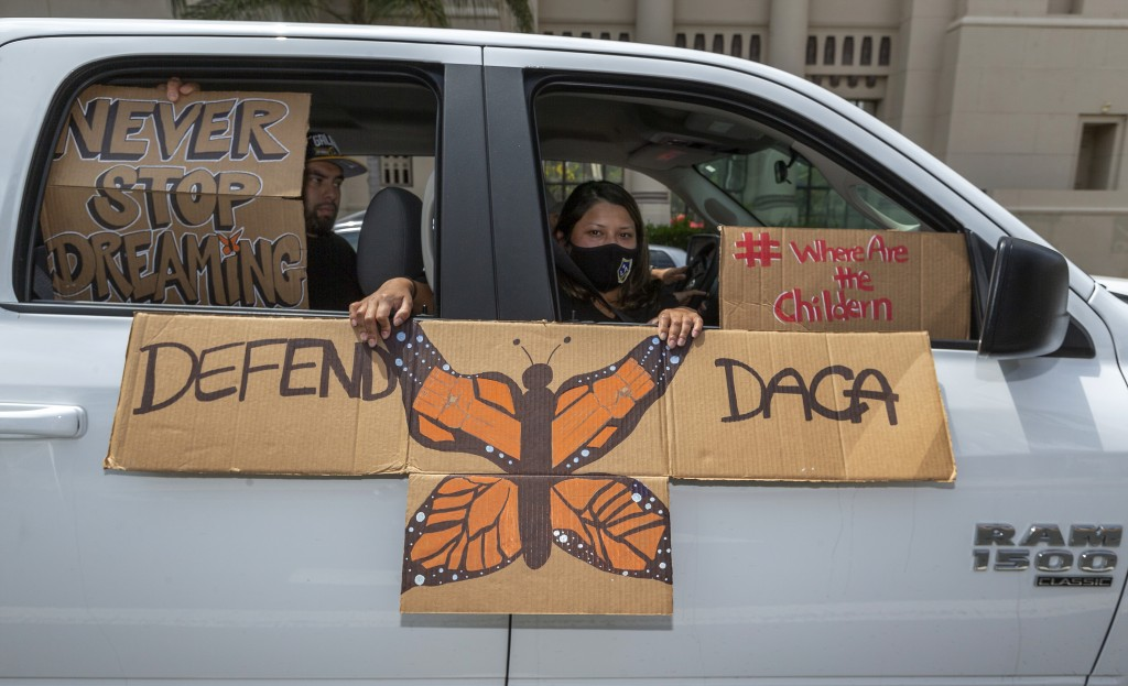 FILE - In this June 18, 2020, file photo, people hold signs during a vehicle caravan rally to support the Deferred Action for Childhood Arrivals Progr...