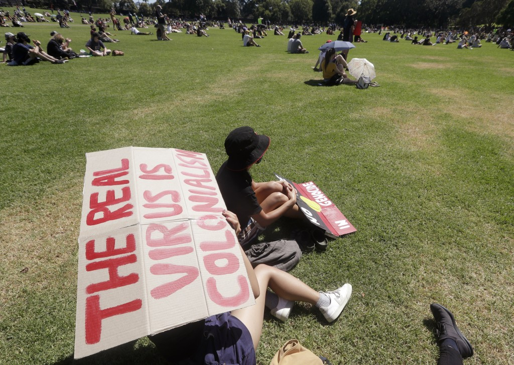 A protester holds a sign in a social distanced crowd during an Aboriginal-lead Invasion Day rally on Australia Day in Sydney, Tuesday, Jan. 26, 2021. ...