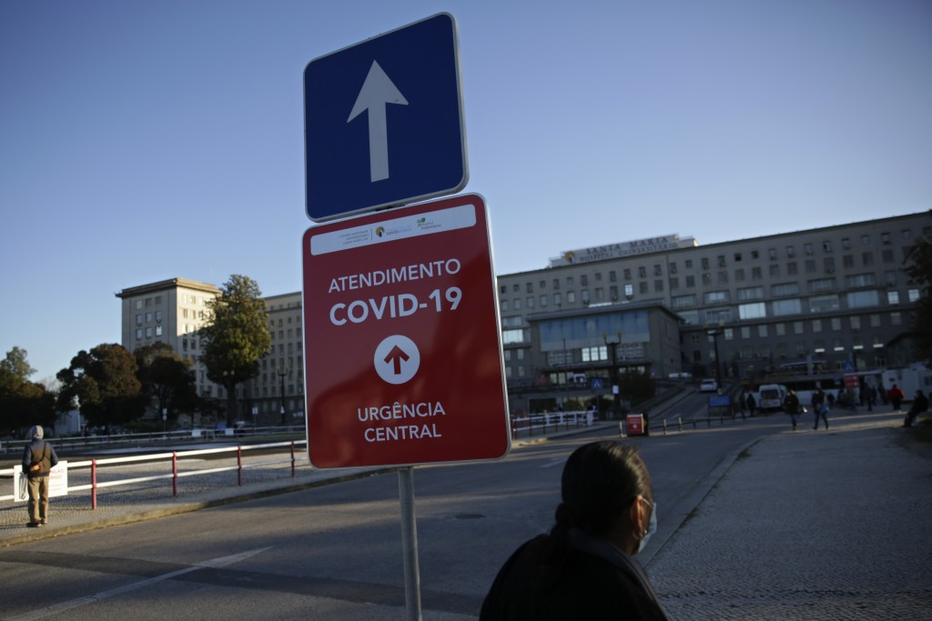 FILE - In this Jan. 18, 2021, file photo, a sign shows the way to the COVID-19 emergency ward at the Santa Maria hospital in Lisbon. In its fight agai...