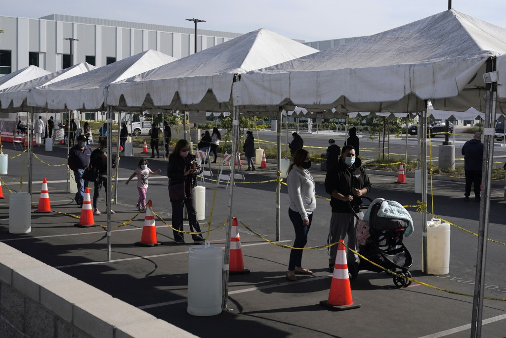 FILE - In this Jan. 7, 2021, file photo, people line up at a COVID-19 walk-up testing site on the Martin Luther King Jr. Medical Campus in Los Angeles...