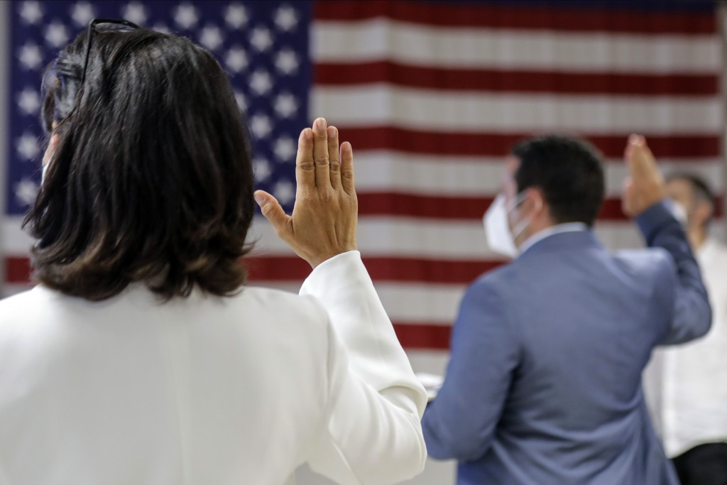 FILE- In this July 2, 2020, file photo, people take the oath of citizenship during a naturalization ceremony at U.S. Citizenship and Immigration Servi...