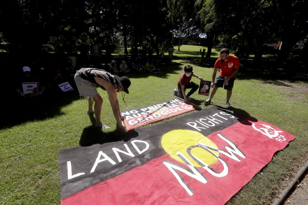 Protesters arrange signs in a social distanced crowd during an Aboriginal-lead Invasion Day rally on Australia Day in Sydney, Tuesday, Jan. 26, 2021. ...