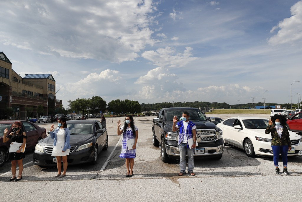 FILE - In this June 26, 2020, file photo, people raise their hands while taking the Oath of Allegiance during a drive-thru naturalization ceremony at ...