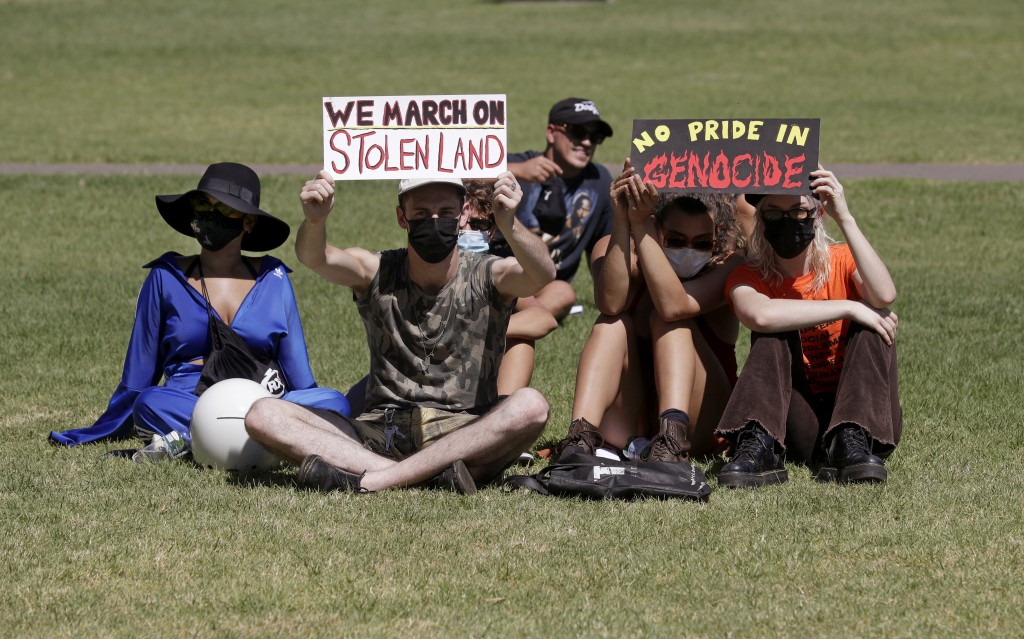 Protesters hold signs in a social distanced crowd during an Aboriginal-lead Invasion Day rally on Australia Day in Sydney, Tuesday, Jan. 26, 2021. Man...