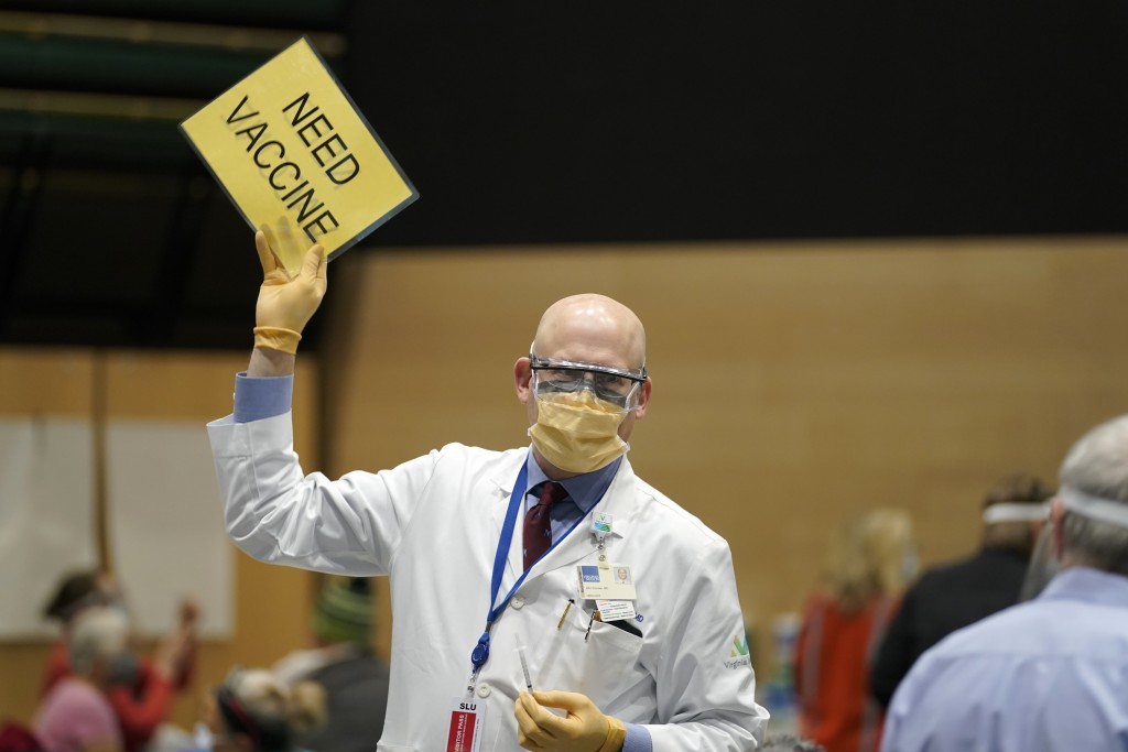 "Dr. John Corman, the chief clinical officer for Virginia Mason Franciscan Health, holds a sign that reads ""Need Vaccine"" to signal workers to bring hi..."