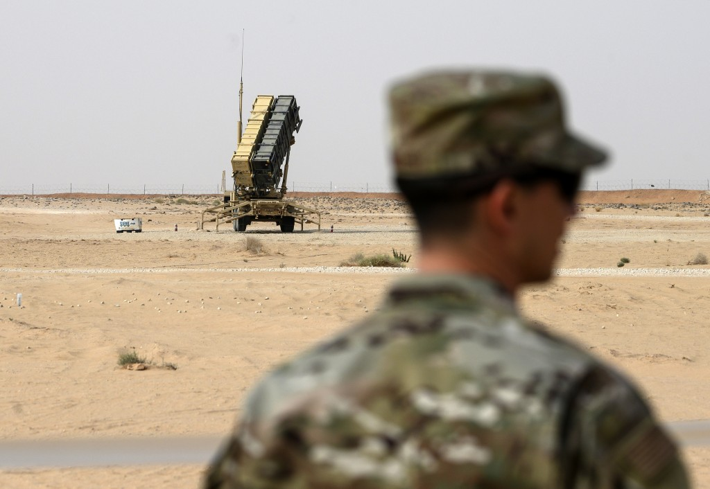 FILE - In this Feb. 20, 2020 file photo, a member of the U.S. Air Force stands near a Patriot missile battery at the Prince Sultan Air Base in al-Khar...