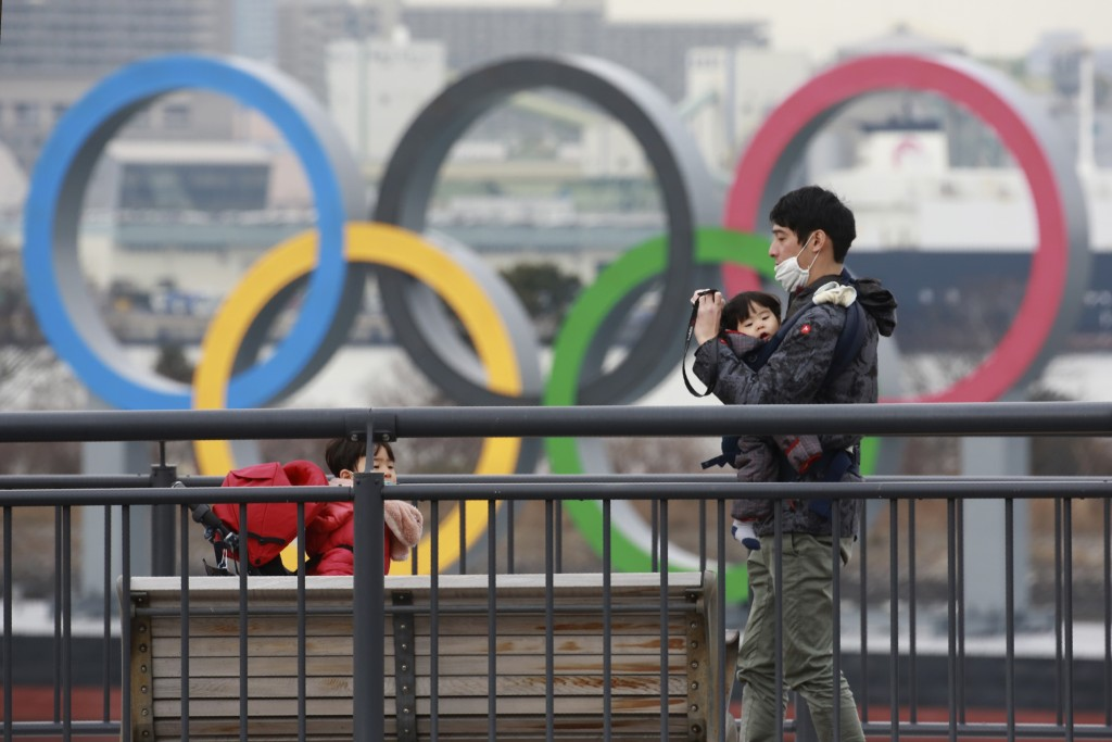 People wearing face masks to protect against the spread of the coronavirus stand at the Odaiba waterfront as Olympic rings is seen in the background i...