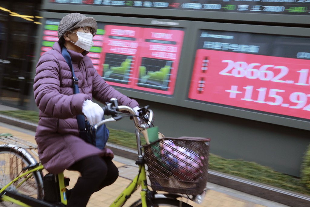 A woman cycles past by an electronic stock board of a securities firm in Tokyo, Wednesday, Jan. 27, 2021. Stocks were mixed in Asia on Wednesday after...
