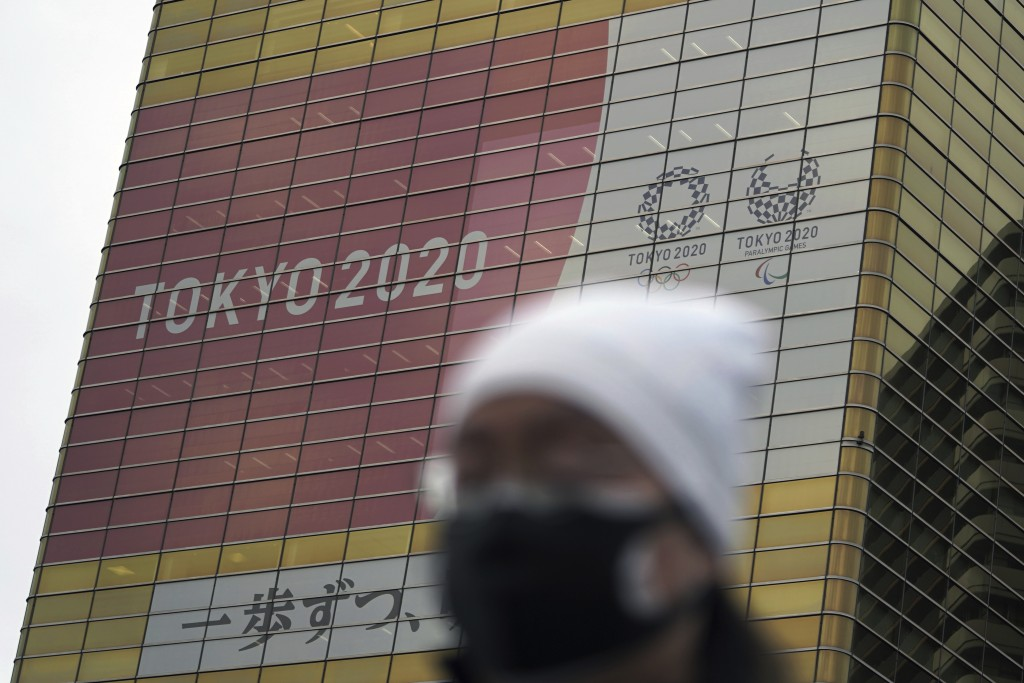 A man wearing a protective mask to help curb the spread of the coronavirus walks near a banner of the Tokyo 2020 Olympics and Paralympics Wednesday, J...