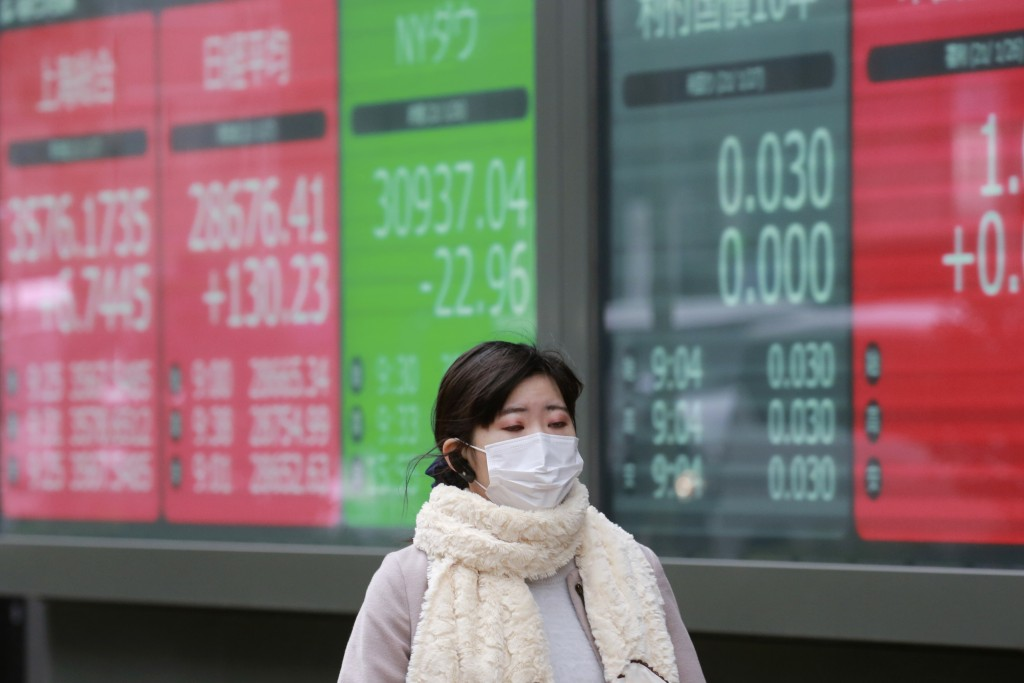 A woman walks by an electronic stock board of a securities firm in Tokyo, Wednesday, Jan. 27, 2021. Stocks were mixed in Asia on Wednesday after a lac...