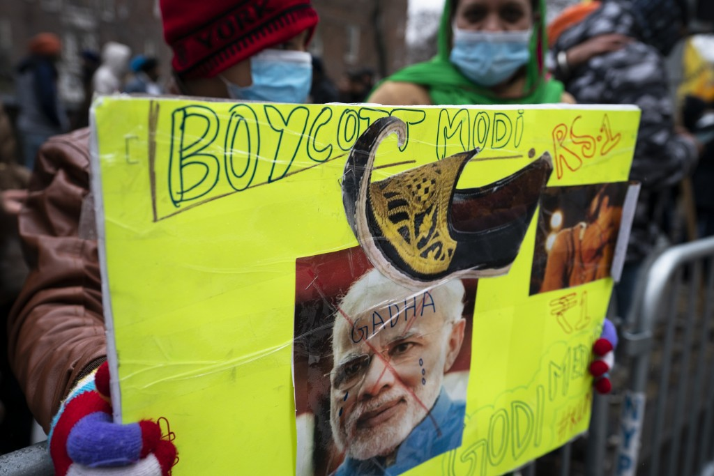 Protesters hold signs on police barricades outside the Consulate General of India, Tuesday, Jan. 26, 2021, in the Manhattan borough of New York. Tens ...