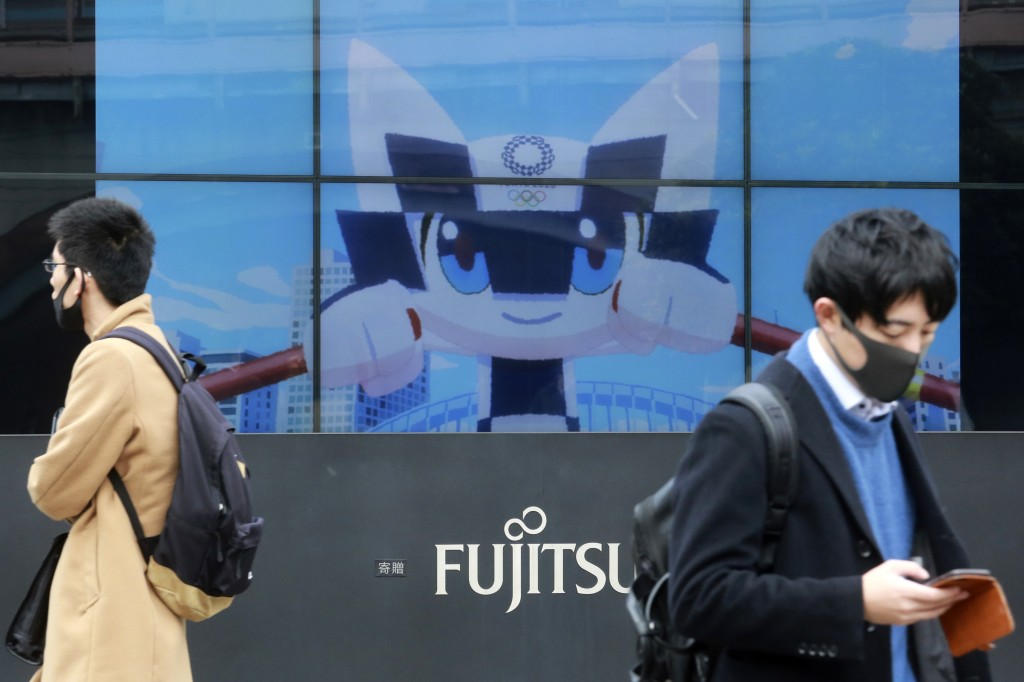 People walk by a TV monitor showing the Tokyo 2020 Olympics promotion, in Tokyo, Wednesday, Jan. 27, 2021.(AP Photo/Koji Sasahara)