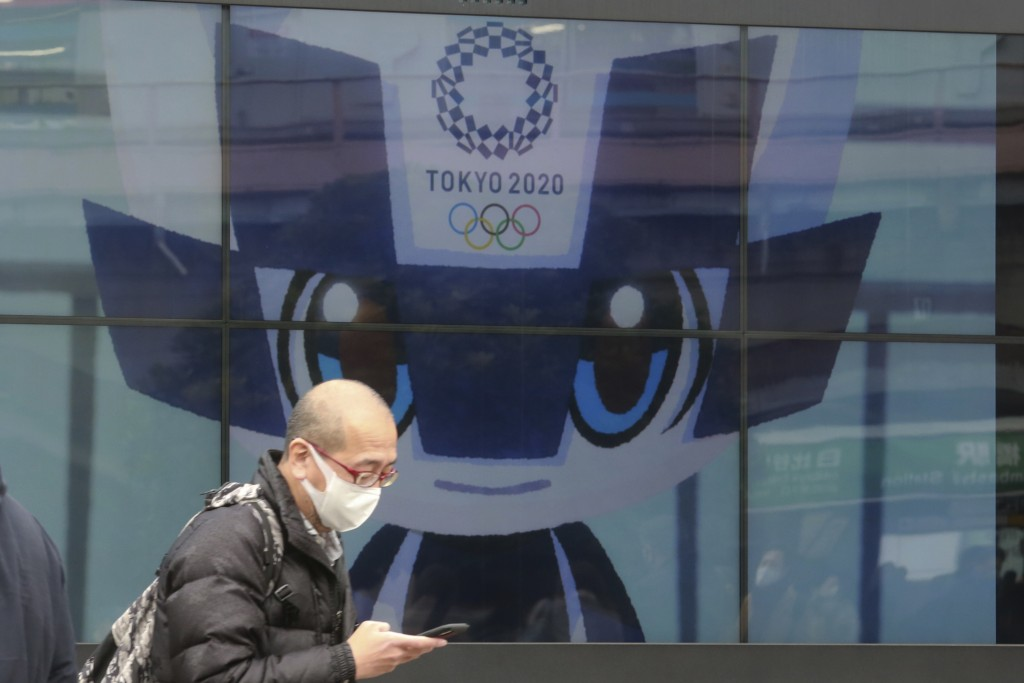 A man walks by an electric monitor promoting the Tokyo 2020 Olympics planned to start in the summer of 2021, in Tokyo, Wednesday, Jan. 27, 2021. (AP P...