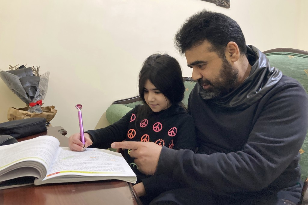 Syrian refugee Mahmoud Mansour, 47, helps his youngest daughter Sahar, 8, with her homework at his rented apartment in Amman, Jordan, Wednesday, Jan. ...