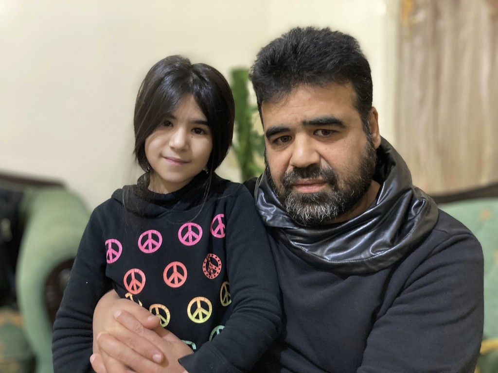 Syrian refugee Mahmoud Mansour, 47, sits with his youngest daughter Sahar, 8, at his rented apartment in Amman, Jordan, Wednesday, Jan. 20, 2021. Pres...