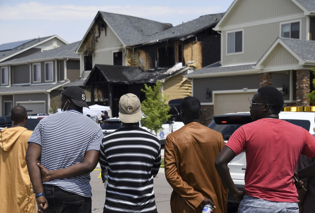 FILE - In this Aug. 5, 2020, file photo, people look at a house where five people were found dead after a fire in Denver. Three teenagers have been ar...