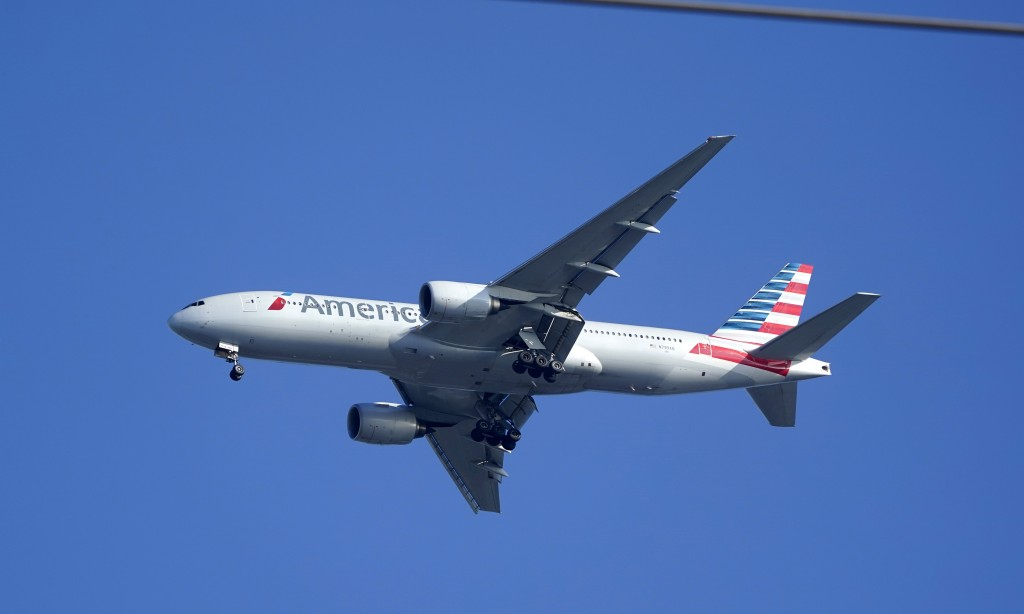 An American Airlines Boeing 777 is framed by utility wires as it prepares to land at Miami International Airport, Wednesday, Jan. 27, 2021, in Miami. ...