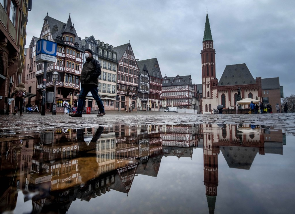 A man wears a face mask as he walks over the Roemerberg square in Frankfurt, Germany, Thursday, Jan. 28, 2021. Further restrictions to avoid the outsp...