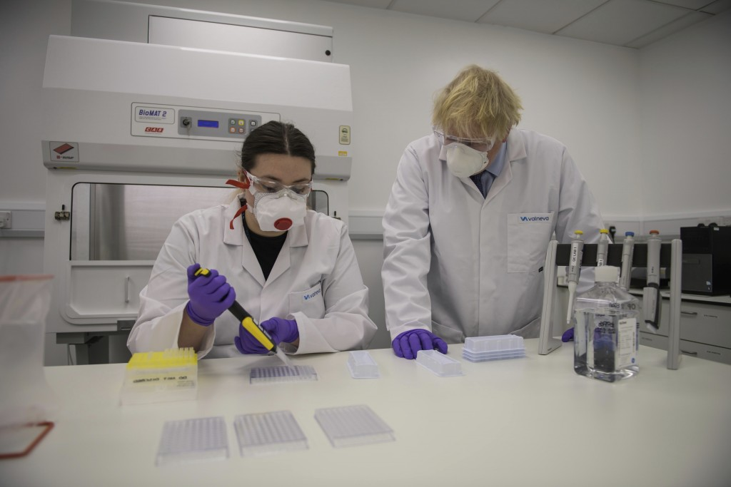 Britain's Prime Minister Boris Johnson with quality control technician Kerri Symington, visits the French biotechnology laboratory Valneva in Livingst...