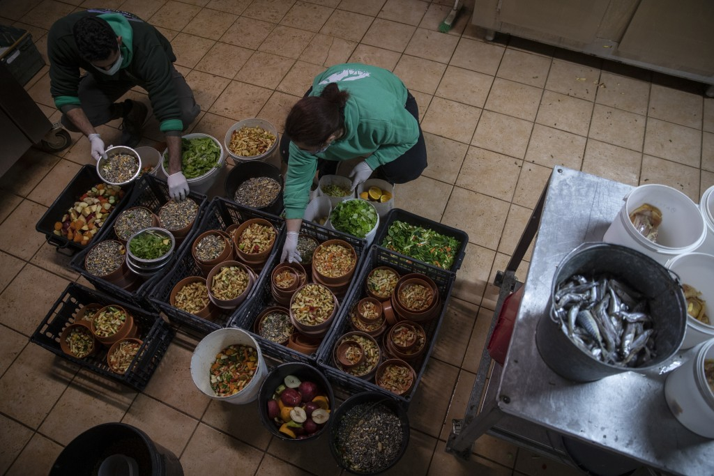 Zoo keepers Alexis left and Christina prepare food for the animals in the Attica Zoological Park in Spata, near Athens, on Tuesday, Jan. 26, 2021. (AP...