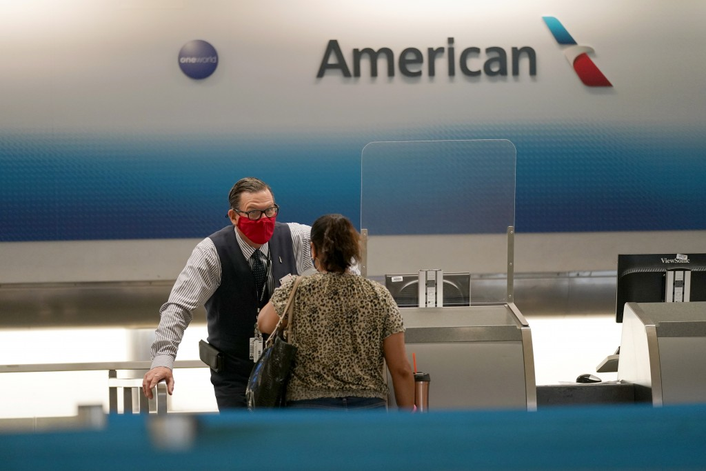 FILE - In this Sept. 30, 2020 file photo, American Airlines ticket agent Henry Gemdron, left, works with a customer at Miami International Airport dur...