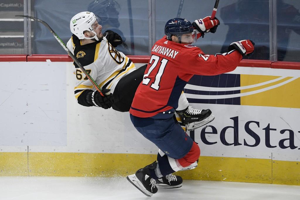 Washington Capitals right wing Garnet Hathaway (21) checks Boston Bruins defenseman Jakub Zboril (67) during the first period of an NHL hockey game, M...